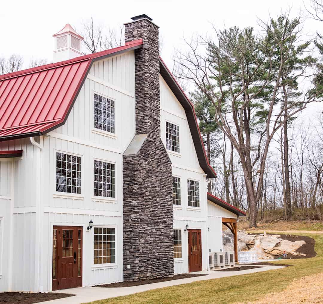 white barn red roof stone chimney